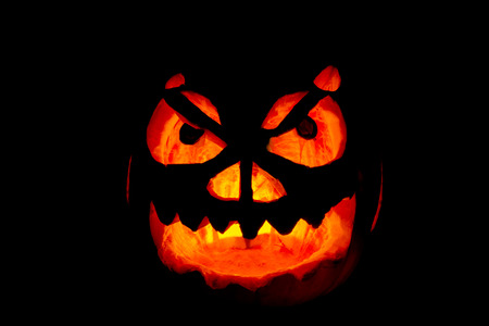 lighting background: Lighting homemade carved Halloween pumpkin with black background Stock Photo