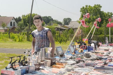 marketeer: DOMBOVAR, HUNGARY - JULY 12. 2015 - Gypsy marketeer boy in a rural Sunday marketplace in Hungary