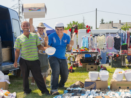 marketeer: DOMBOVAR, HUNGARY - JULY 12. 2015 - Gypsy marketeers in a rural Sunday marketplace in Hungary