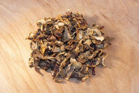 cantharellus: Heap of dried golden chanterelle (Cantharellus cibarius) on a wooden plate Stock Photo