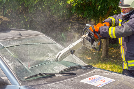 szeged: SZEGED, HUNGARY - JULY 25. 2015 - A fireman breaks the windscreen in a disaster prevention practice in Szeged Zoo,