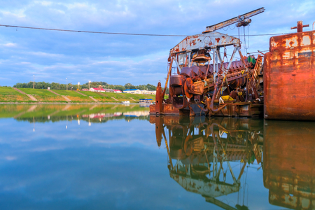 Old and rusty dredge ship on the harbour of the Tisza River, near Szeged, Hungary