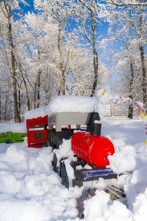Snow covered red Christmas train in a winter forest