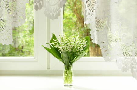 Bouquet of lily of the valley on the windowsill Stock Photo