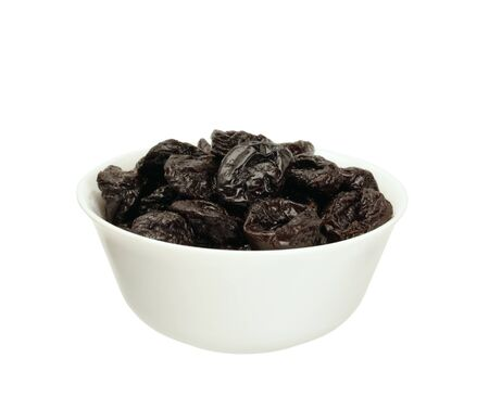Dried plums or prunes  in a bowl isolated on white
