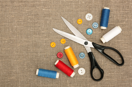 Sewing concept  Scissors, colorful  bobbin thread and buttons