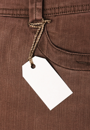 Blank paper label tag on brown jeans