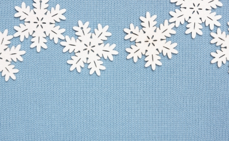 winter background  knitted fabric and snowflakes