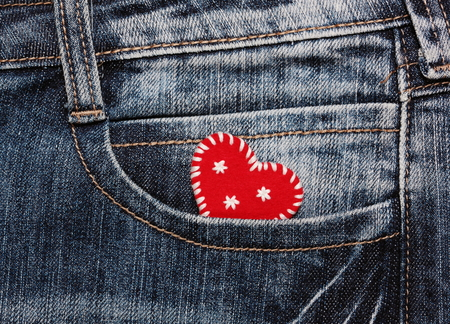 handmade felt red Christmas heart with embroidered snowflakes in jeans pocket photo