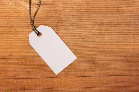 Blank paper label tag on wooden  photo