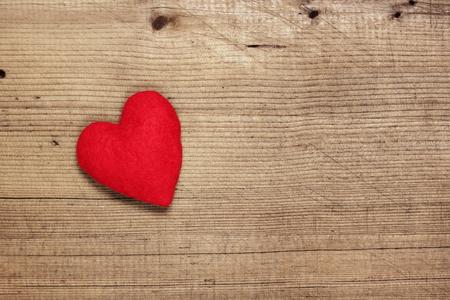 Red  felt heart on wooden background