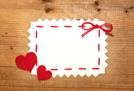 Blank Valentines card with felt hearts on wooden