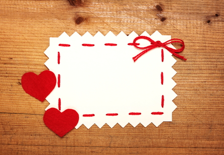 Blank Valentines card with felt hearts on wooden background