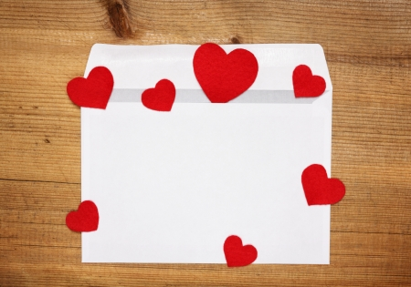 Envelope with red hearts for valentine day on wooden background
