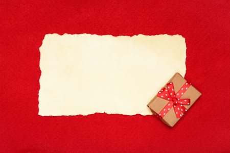 Blank and vintage gift box with ribbon bow on red felt background