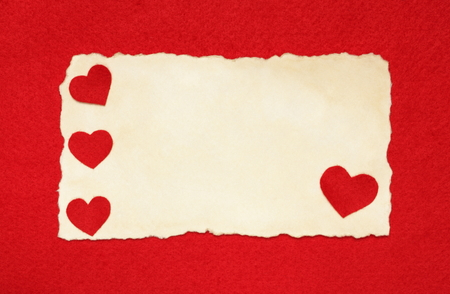 Blank Valentines card with felt hearts on red felt background Stock Photo
