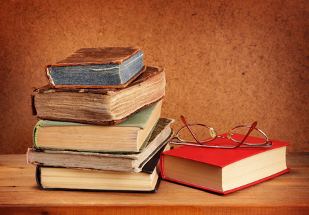 Books stack and glasses on wooden table photo
