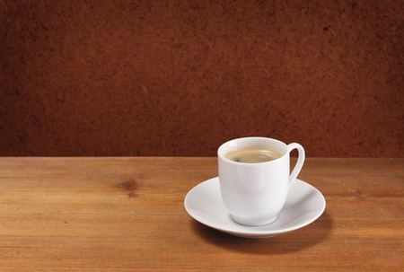 Coffee cup and saucer on wooden table  Dark background   Stock Photo