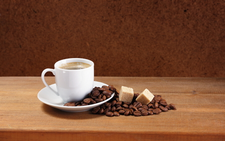Coffee cup on saucer, beans and sugar on a wooden table  Dark background   photo