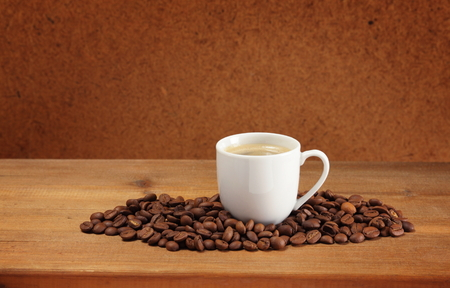 Coffee beans and cup on a wooden table  Dark background   Stock Photo