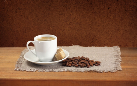 Coffee beans, cup, saucer, sugar, napkin on wooden table  Dark background  photo
