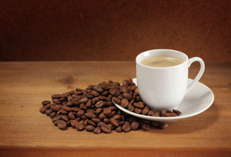 Coffee beans, cup, saucer and napkin on wooden table  Dark background  Stock Photo