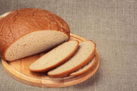 cut loaf of rye bread  on wooden board