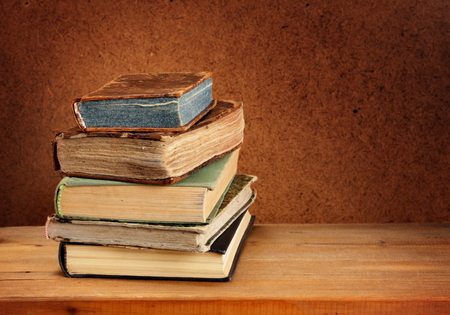 Stack of old books on wooden table