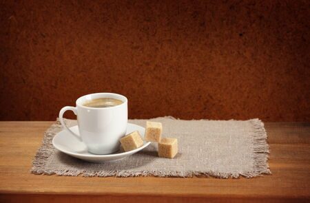 Coffee cup, saucer, sugar, napkin on wooden table  Dark background  Stock Photo
