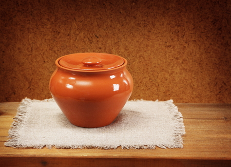 Clay pot for cooking and napkin on wooden table