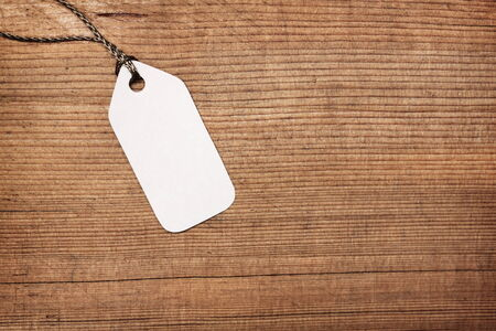 Blank paper label tag on wooden background