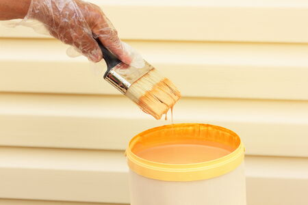 hand dipping paint brush into a can of wood stain