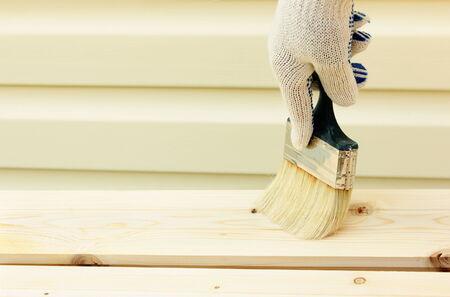 hand with paintbrush on wood Stock Photo
