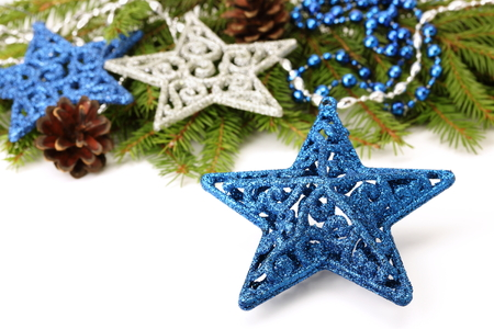 Blue glitter Christmas star decoration and Christmas tree branch on white