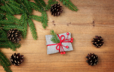 Vintage rural gift and Christmas tree branch on wooden background Stock Photo