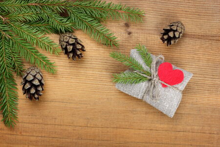 Christmas card: Vintage rural gift  and Christmas tree branch on wooden background Stock Photo