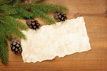 Blank Old Paper Sheet with Christmas tree branches and cones on wooden background Stock Photo