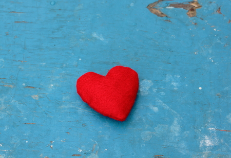 Red  felt heart on navy blue wooden background