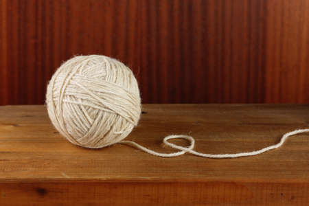 snugly: Ball of rough rustic yarn on dark wooden background Stock Photo