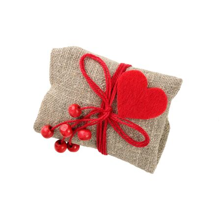 vintage gift in sacking with red heart and beads, isolated on white Stock Photo
