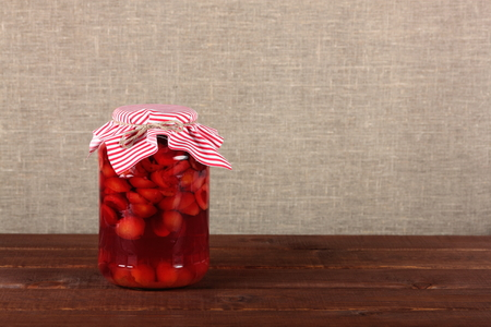Glass jar with canned fruits on rustic wooden table. Copy space background