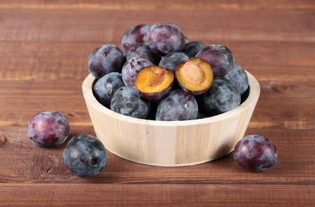 Fresh juicy plums in wooden round bowl