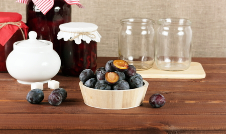Canning. Fresh and preserved plums on rustic wooden table.