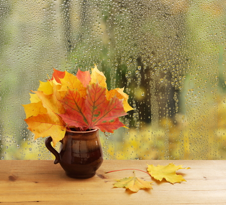 Bouquet of autumn leaves on window sill Stock Photo