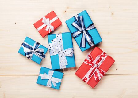 wrapped gift boxes with ribbon bows on wooden board