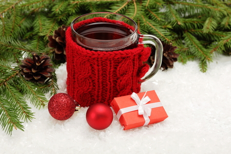 Christmas card. Cup of tea, Christmas tree branches, gift and balls Stock Photo