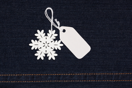 Blank paper label tag and snowflake on dark blue jeans