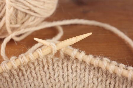Two bamboo knitting needles in process of knitting Stock Photo