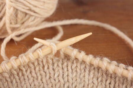 plain stitch: Two bamboo knitting needles in process of knitting Stock Photo