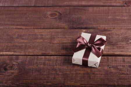 wrapped gift box with ribbon bow on dark wooden board